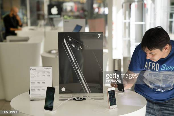 A customer views an Apple Inc iPhone at a Maxim Store in Buenos Aires Argentina on Friday April 7 2017 Apple Inc's iPhone will be sold widely in...