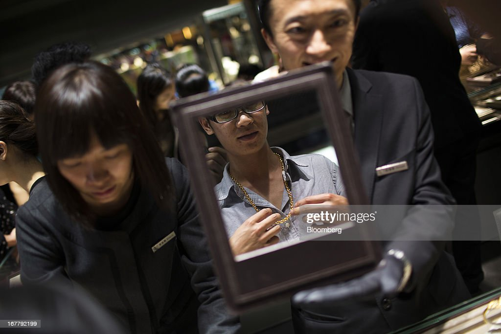 A customer views himself in a mirror as he tries on a gold chain at a Chow Sang Sang Holdings International Ltd. jewelry store in the Mongkok district of Hong Kong, China, on Tuesday, April 30, 2013. Chow Sang Sang said that jewelry sales at its 44 shops in Hong Kong more than doubled in the two weeks ended April 27 from a year ago. Photographer: Lam Yik Fei/Bloomberg via Getty Images
