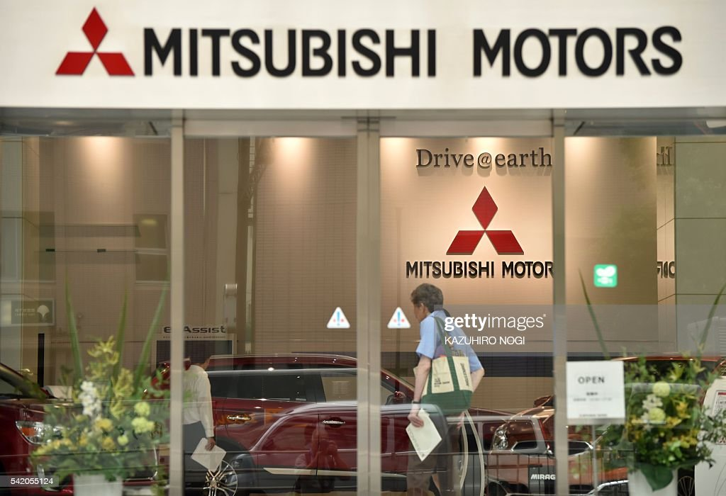 A customer visits a Mitsubishi Motors showroom in Tokyo on June 22 2016 Mitsubishi Motors expects a net loss of 139 billion USD in the year to March...
