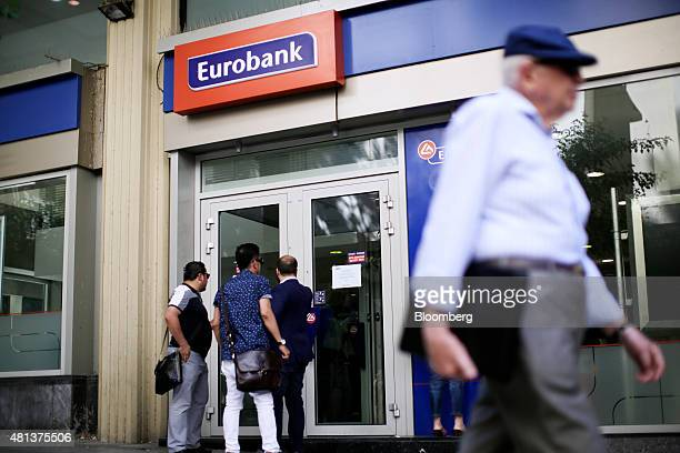 Customer wait to enter a Eurobank Ergasias SA bank branch in Athens Greece on Monday July 20 2015 German Chancellor Angela Merkel held out the...