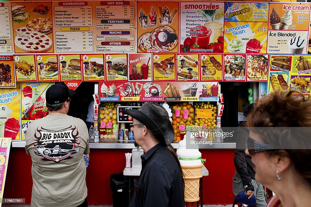 A customer waits for his order in front of a food stand at Venice Beach in Los Angeles, California, U.S., on Wednesday, Aug. 14, 2013. Overall U.S. tourism-related sales increased 6.8% in the second quarter of 2013 as compared to 2012. Photographer: Patrick T. Fallon/Bloomberg via Getty Images