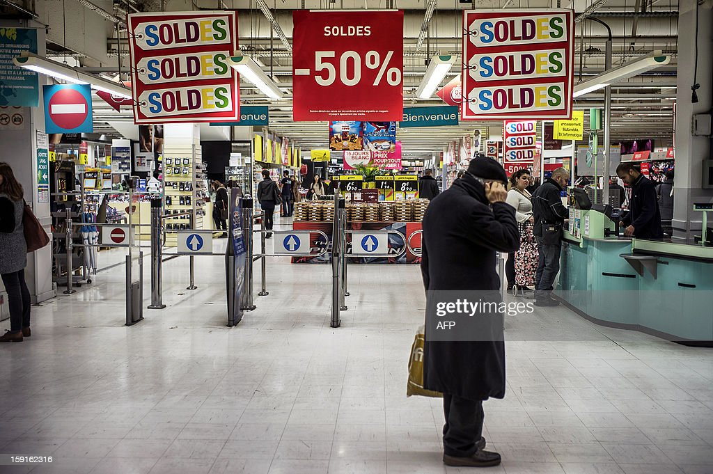 A customer waits in front of the entrance of a supermarket in Lyon, on January 9, 2013, during the official start of winter sales.