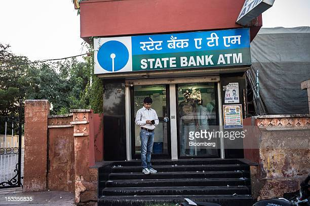 A customer waits outside a State Bank of India automated teller machine branch in Jaipur Rajasthan India on Wednesday Oct 3 2012 The Indian economy...