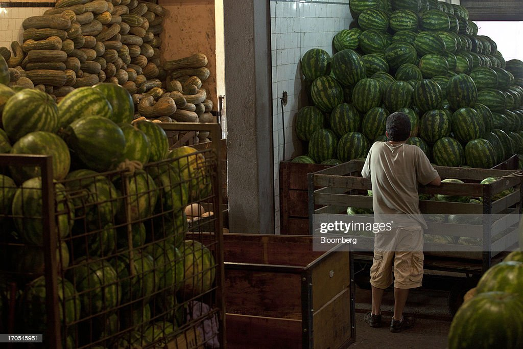 A customer waits to be served at a watermelon stall at a market in Rio de Janeiro, Brazil, on Thursday, June 13, 2013. Brazilian retail sales rose in April at less than half the pace economists forecast as inflation erodes purchasing power, complicating the governments effort to boost growth. Photographer: Dado Galdieri/Bloomberg via Getty Images