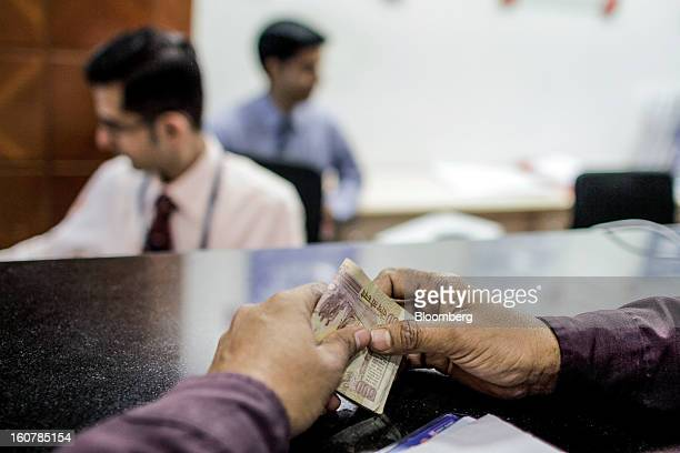 A customer waits to deposit Indian 500 rupee banknotes at a HDFC Bank Ltd bank branch in Mumbai India on Friday Feb 1 2013 HDFC Bank India's...