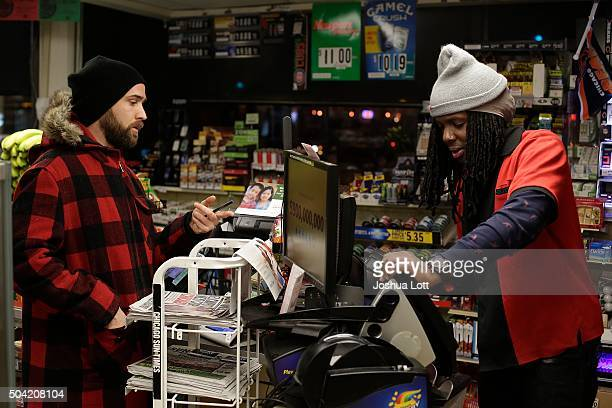 A customer waits to receive his Powerball ticket from a 7Eleven store clerk January 9 2016 in Chicago Illinois The Powerball Jackpot Surged to a...
