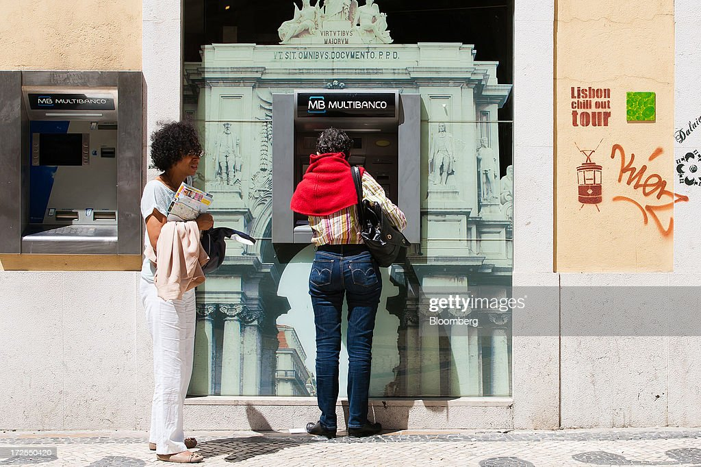 A customer waits to use an automated teller machine (ATM) operated by the Multibanco interbank network in Lisbon, Portugal, on Wednesday, July 3, 2013. Portuguese borrowing costs topped 8 percent for the first time this year after two ministers quit, signaling the government will struggle to implement further budget cuts as its bailout program enters its final 12 months. Photographer: Mario Proenca/Bloomberg via Getty Images