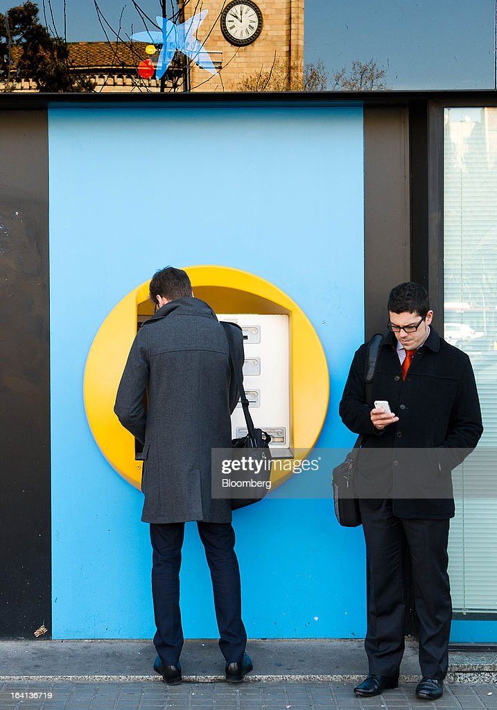 A customer waits to withdraw cash from an automated teller machine (ATM) outside a CaixaBank SA branch in Barcelona, Spain, on Wednesday, March 20, 2013. Officials from the troika of international creditors -- the ECB, the International Monetary Fund and the European Commission -- are in Cyprus discussing further capital controls and possibly extending a bank holiday to the end of the week, a European official familiar with the talks said on condition of anonymity because the discussions are confidential. Photographer: David Ramos/Bloomberg via Getty Images