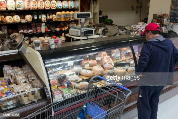 A customer waits while an employee weights some ham at the delicatessen counter of a Superama grocery store in the La Condesa neighborhood of Mexico...