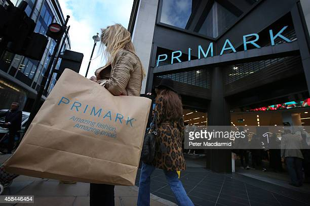 A customer waits with her purchases outside Primark's flagship store on Oxford Street on November 5 2014 in London England Retail giant Marks and...