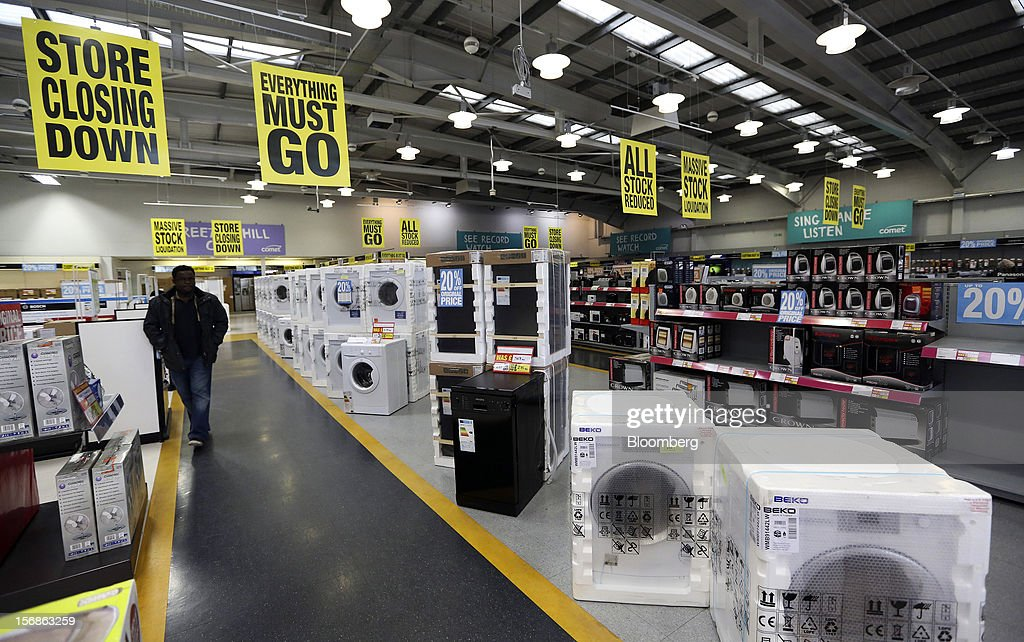 A customer walks beneath 'Store Closing Down' and ' Everthing Must Go' signs as he passes a display of reduced-price household appliances inside a Comet electronics store in Slough, U.K., on Friday, Nov. 23, 2012. Comet, a U.K. electronics chain, appointed Deloitte LLP as insolvency administrator, less than a year after being bought by private-equity firm OpCapita LLP. Photographer: Chris Ratcliffe/Bloomberg via Getty Images