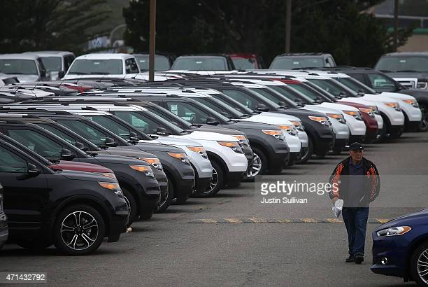 A customer walks by rows of cars on the sales lot at Serramonte Ford on April 28 2015 in Colma California Ford Motor Co reported a 66 percent drop in...