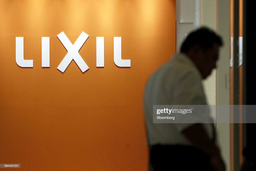 A customer walks in front of the Lixil Group Corp. logo at the company's showroom in Tokyo, Japan, on Friday, Oct. 11, 2013. Lixil and Development Bank of Japan agreed on Sept. 26 to buy bathroom-fixtures maker Grohe Group, valuing the German company at 3.06 billion euros ($4.1 billion). Photographer: Kiyoshi Ota/Bloomberg via Getty Images