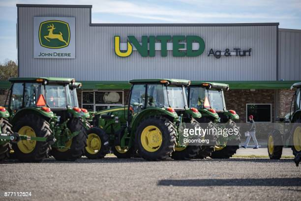 A customer walks near Deere Co John Deere tractors on display at a United Ag Turf dealership in Waco Texas US on Monday Nov 20 2017 Deere Co is...