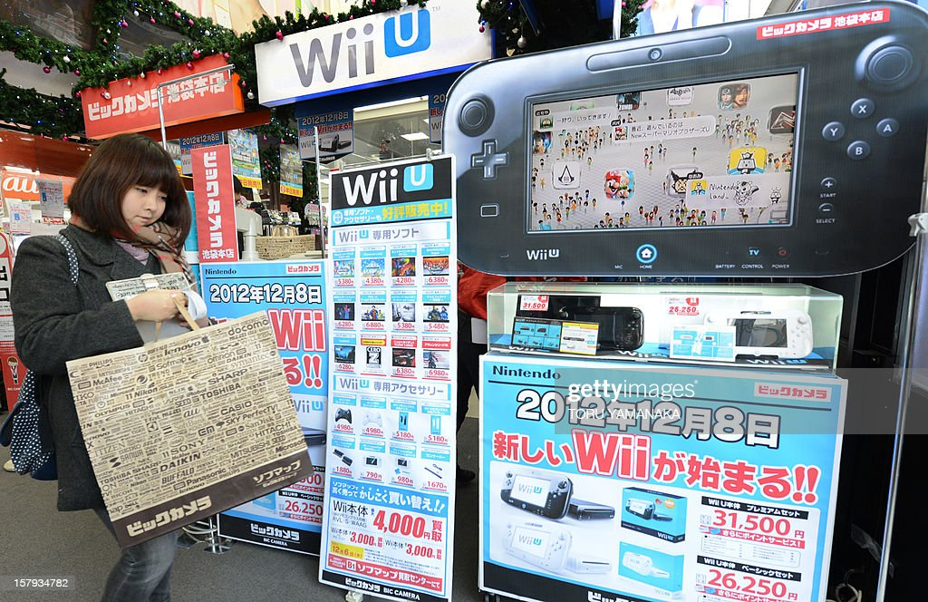 A customer walks past a console display (R) after purchasing Japanese electronics titan Nintendo's new videogame console 'Wii U' at a shop in Tokyo on December 8, 2012. Nintendo released the new console in Japan on December 8 and is hoping for a repeat of the runaway success it had with original Wii consoles, which lured legions of 'casual gamers' into the videogame world with the introduction of motion-sensing controls. AFP PHOTO/Toru YAMANAKA
