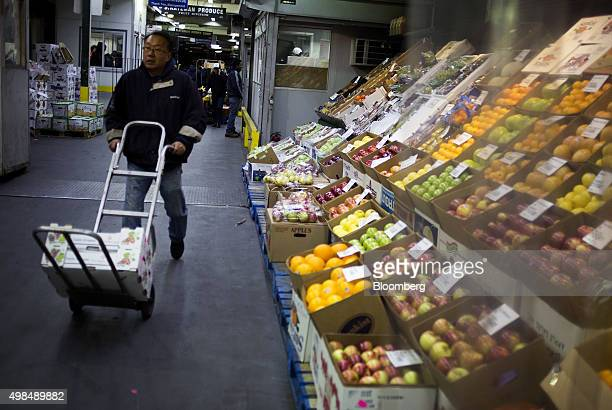 A customer walks past a display of produce at the Hunts Point Terminal Produce Market in the Bronx borough of New York US on Monday Nov 23 2015 The...
