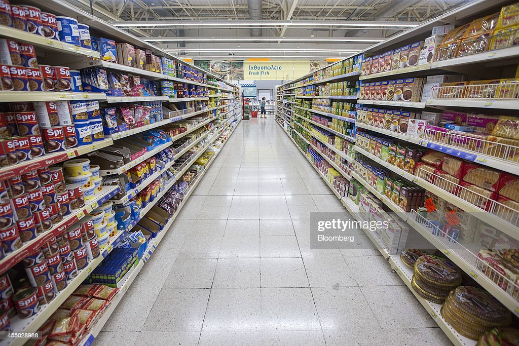 A customer walks past a food aisle inside a Carrefour SA supermarket part of the Marinopoulos Group in Limassol Cyprus on Monday Sept 8 2014 The...