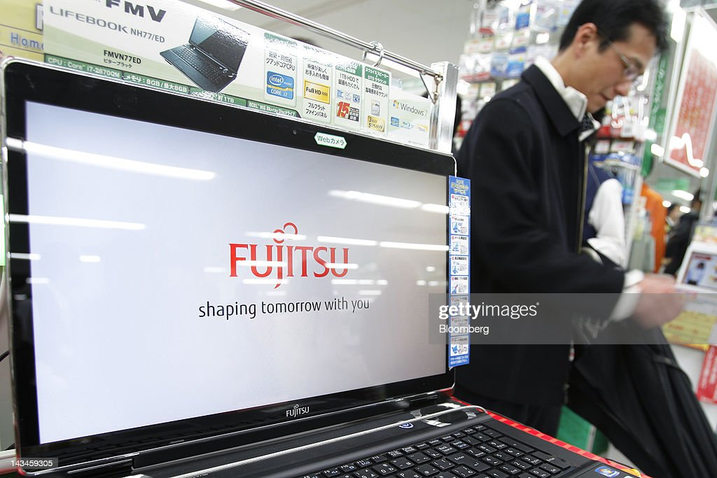 A customer walks past a Fujitsu Ltd. FMV laptop computer displaying the company's logo on its screen at the Labi Ofuna electronics store, operated by Yamada Denki Co., in Yokohama City, Kanagawa Prefecture, Japan, on Friday, April 27, 2012. Fujitsu Ltd. forecast the first increase in profit in three years on increasing sales of services and equipment related to cloud computing and on cost cuts including the sale of its chip factory in Iwate, Japan. Photographer: Kiyoshi Ota/Bloomberg via Getty Images