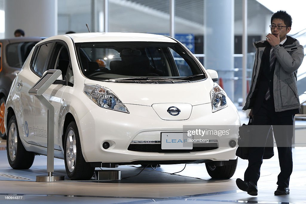 A customer walks past a Nissan Motor Co. Leaf electric vehicle (EV) displayed at the company's showroom in Yokohama, Kanagawa Prefecture, Japan, on Friday, Feb. 8, 2013. Nissan, Japan's second-biggest carmaker, reported third-quarter profit that fell short of analysts' estimates, after sales tumbled in China and new models trailed competitors in the U.S. Photographer: Kiyoshi Ota/Bloomberg via Getty Images