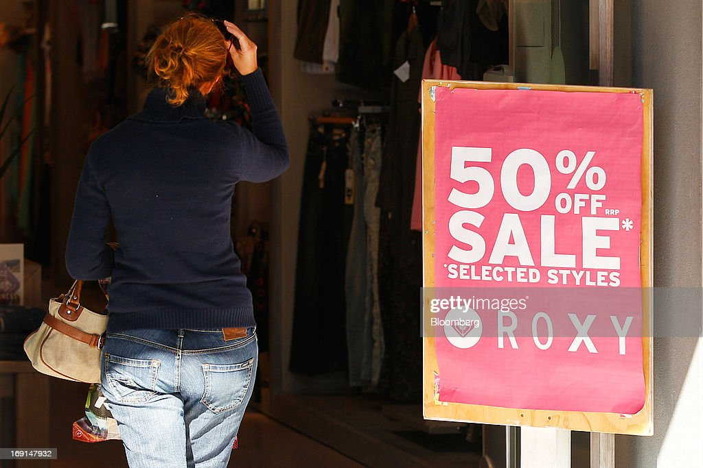 A customer walks past a sale sign as she enters a Quiksilver Inc. Roxy store in the Manly area of Sydney, Australia, on Sunday, May 19, 2013. The Reserve Bank of Australia cut its benchmark interest rate to a record low this month to boost businesses weakened by the currency's sustained strength, even as households reacted to earlier reductions. Photographer: Brendon Thorne/Bloomberg via Getty Images