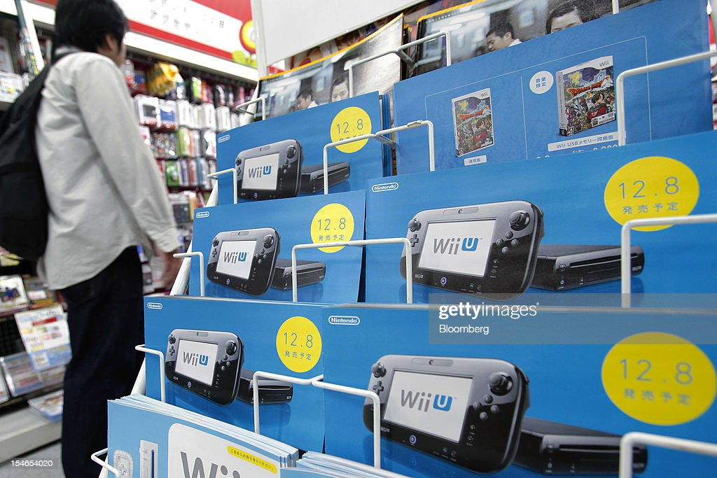 A customer walks past brochures advertising Nintendo Co.'s Wii U game console at an electronics store in Tokyo, Japan, on Wednesday, Oct. 24, 2012. Nintendo, the world's largest maker of video-game machines, cut its full-year profit forecast amid weaker demand for its 3DS handheld player and a strong yen. Photographer: Kiyoshi Ota/Bloomberg via Getty Images