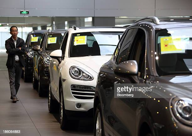 A customer walks past Porsche AG Cayenne sport utility vehicles displayed at the Porsche Centre Shanghai Minhang showroom in Shanghai China on Friday...