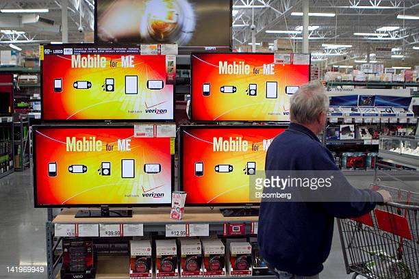 A customer walks past Samsung Electronic Co Ltd LED televisions at a BJ's Wholesale Club Inc store in Falls Church Virginia US on Tuesday March 27...