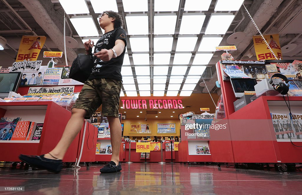 A customer walks past shelves in a Tower Records Japan Inc. store in Tokyo, Japan, on Monday, July 1, 2013. Music sales in the country rose for the first time in five years, led by tunes delivered on CDs and other physical media, bucking the trend in developed markets as cheaper downloads gain ground. Physical media made up 82 percent of Japanese music sales last year, versus 37 percent in the U.S., said the Recording Industry Association of Japan. Photographer: Yuriko Nakao/Bloomberg via Getty Images
