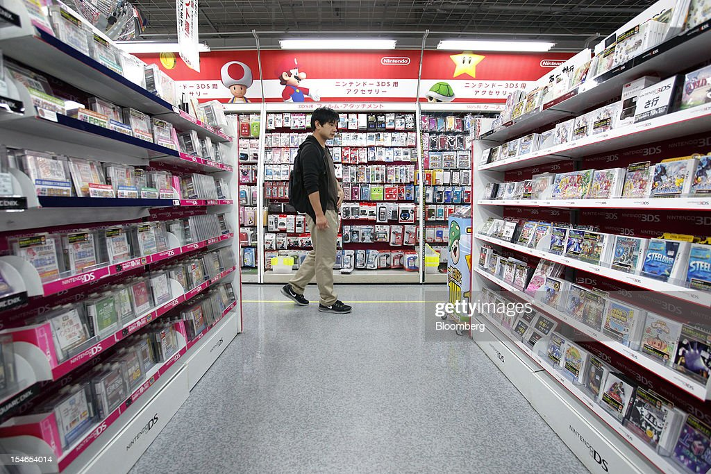 A customer walks past shelves of software titles for Nintendo Co.'s DS, left, and 3DS handheld game consoles at an electronics store in Tokyo, Japan, on Wednesday, Oct. 24, 2012. Nintendo, the world's largest maker of video-game machines, cut its full-year profit forecast amid weaker demand for its 3DS handheld player and a strong yen. Photographer: Kiyoshi Ota/Bloomberg via Getty Images