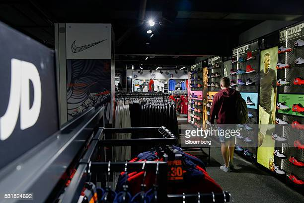 A customer walks past soccer boots and balls at a JD Sports Fashion Plc sportswear retail store on Oxford Street in London UK on Thursday April 28...