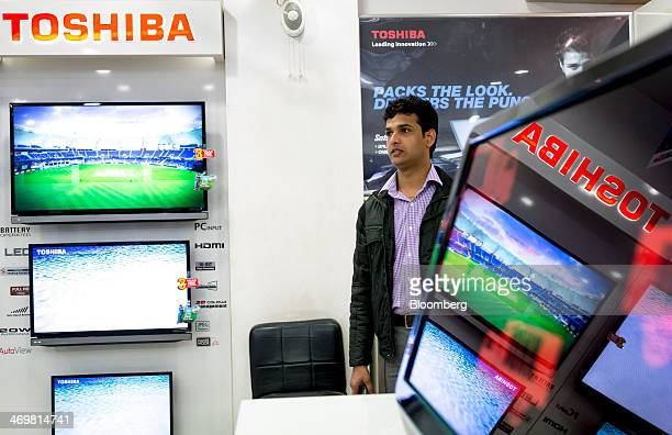 A customer walks past Toshiba Corp televisions at a company store in Nehru Place IT Market a hub for the sale of electronic goods and computer...