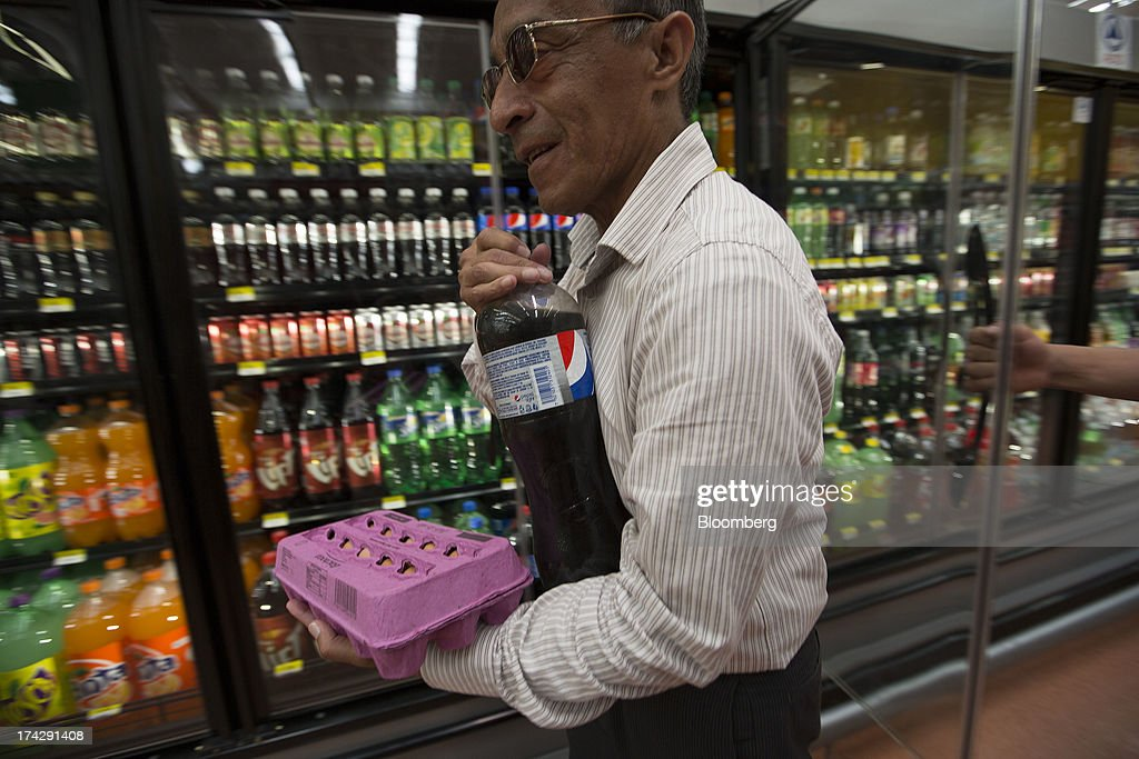A customer walks with a bottle of PepsiCo Inc. soft drink at a store in Mexico City, Mexico, on Monday, July 22, 2013. PepsiCo Inc. is expected to release earnings data on July 24. Photographer: Susana Gonzalez/Bloomberg via Getty Images