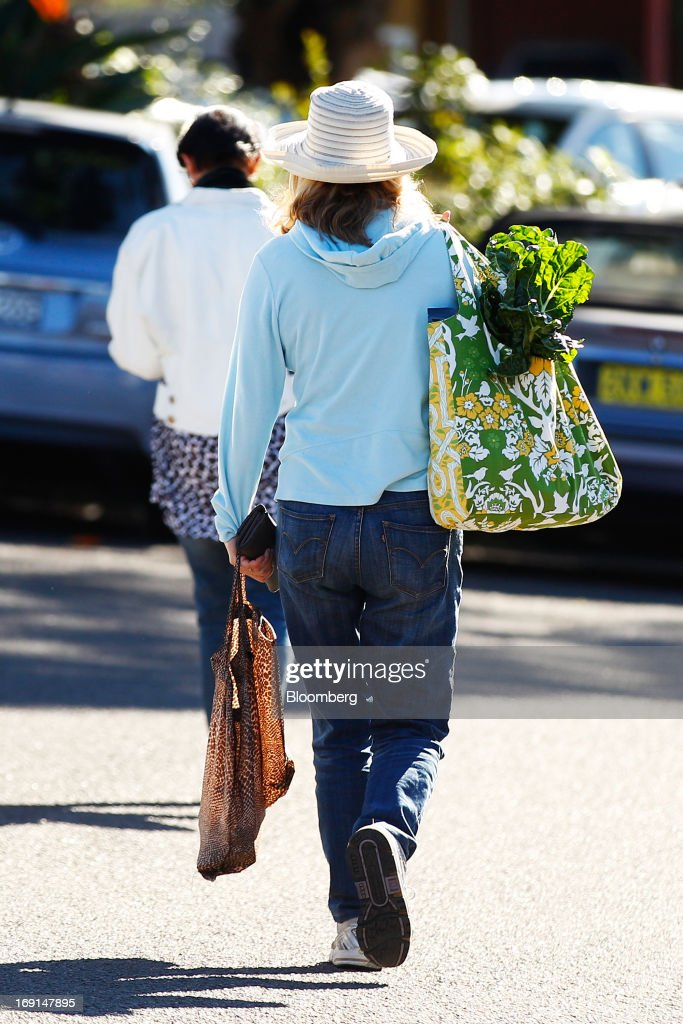 A customer walks with shopping bags filled with produce as she leaves the Frenchs Forest Organic Food Market in Sydney, Australia, on Sunday, May 19, 2013. The Reserve Bank of Australia cut its benchmark interest rate to a record low this month to boost businesses weakened by the currency's sustained strength, even as households reacted to earlier reductions. Photographer: Brendon Thorne/Bloomberg via Getty Images