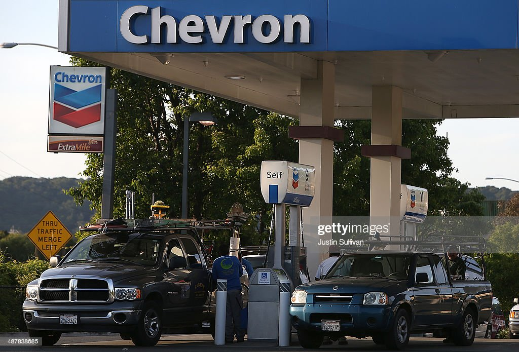 A customer washes his car window at a Chevron gas station on May 2 2014 in Corte Madera California Chevron Corp reported a 27 percent plunge in first...