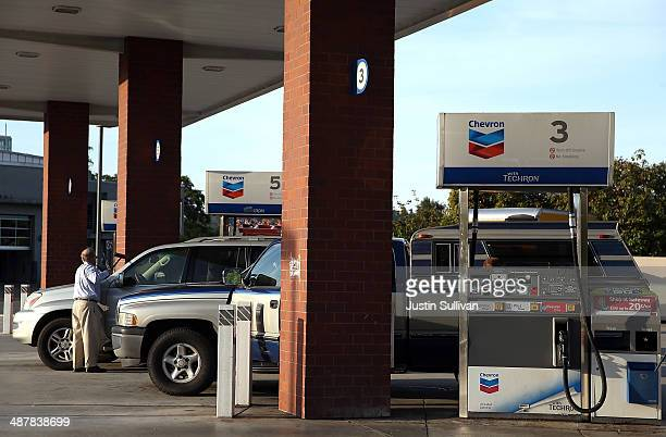 A customer washes his car window at a Chevron gas station on May 2 2014 in Greenbrae California Chevron Corp reported a 27 percent plunge in first...