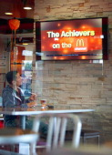 A customer watches television at a McDonald's Corp restaurant in Norwalk California US on Thursday Oct 20 2011 McDonald's Corp aims to roll out a...
