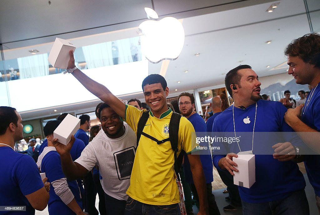 A customer wearing a Brazil soccer jersey poses while celebrating after entering Brazil's first Apple retail store minutes after it opened to the...