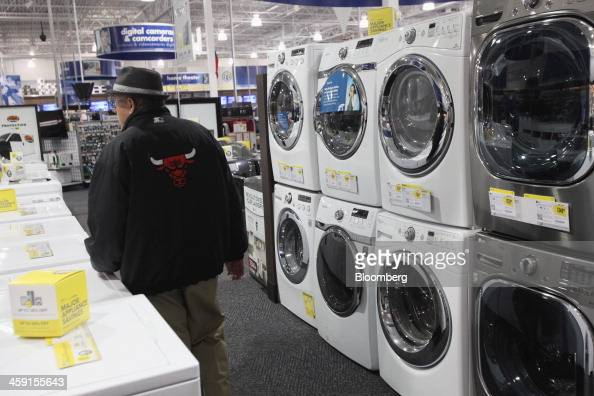 A customer wearing a Chicago Bulls coat walks past washer and dryers at a Best Buy Co store in Northbrook Illinois US on Monday Dec 23 2013 The US...
