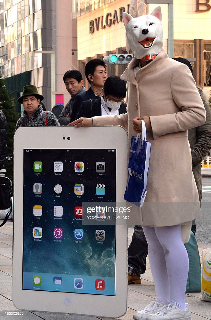 A customer wearing a dog mask displays a model of a large iPad as customers wait outside an Apple store in Tokyo on November 1, 2013, on the day that Apple's new 'iPad Air' tablets are launched. Over 300 customers queued up for the new slim iPad Air as the tablet launched worldwide. AFP PHOTO / Yoshikazu TSUNO