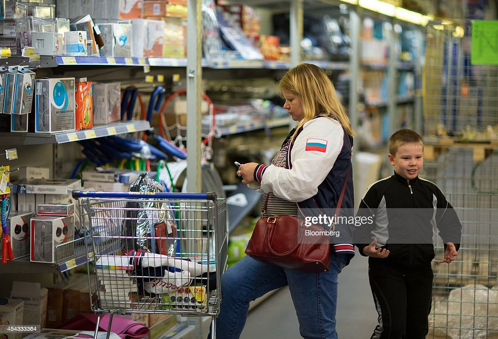 A customer wearing a jacket displaying a colors of the Russian national flag pauses to use a mobile handset while shopping inside a Metro Cash & Carry store, the Russia unit of Metro AG, in Moscow, Russia, on Friday, Aug. 29, 2014. Metro Cash & Carry has warned that domestic food suppliers are trying to increase some food prices as local produce is substituted for EU, Norwegian and U.S. equivalents which have been sanctioned. Photographer: Andrey Rudakov/Bloomberg via Getty Images