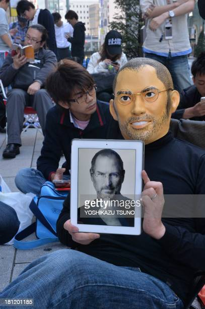 A customer wearing a mask designed to resemble Steve Jobs holds up a portrait of Steve Jobs on his iPad as he queues up to buy Apple's new iPhone 5s...