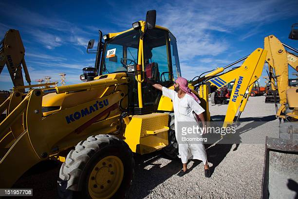 A customer wearing traditional arab 'dishdash' or thawb clothing inspects a Komatsu Ltd excavator for sale at the Ritchie Bros auction for heavy...