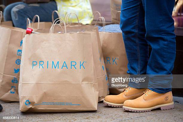 A customer wears Timberland Co boots as he stands with Primarkbranded paper shopping bags outside a Primark clothing store operated by Associated...