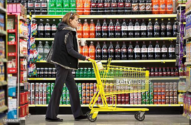 Customer Wendy Rosen pushes a shopping cart past a display of soft drinks at a Dollar General Corp store in Saddle Brook New Jersey US on Saturday...