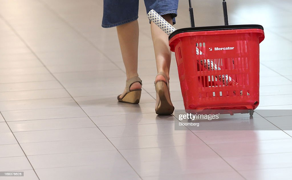A customer wheels a branded shopping cart along an aisle inside a Mercator Poslovni Sistem d.d. supermarket in Ljubljana, Slovenia, on Wednesday, May 8, 2013. In January Mercator reported its first full-year loss in fifteen years as the largest supermarket chain's sales in the Balkans last year suffered during the recession. Photographer: Chris Ratcliffe/Bloomberg via Getty Images