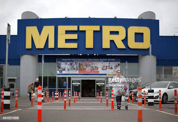 A customer wheels a cart across a parking lot after shopping at a Metro Cash Carry store the Russia unit of Metro AG in Moscow Russia on Friday Aug...