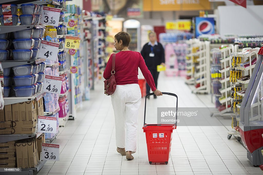 A customer wheels a shopping basket along an aisle inside a Carrefour SA supermarket at the Mall of Cyprus in Nicosia, Cyprus, on Tuesday, March 26, 2013. Controls on capital movements to prevent money from draining out of the banking system -- allowed in exceptional circumstances under European Union law -- will remain for 'a matter of weeks,' Cypriot Finance Minister Michael Sarris said. Photographer: Simon Dawson/Bloomberg via Getty Images