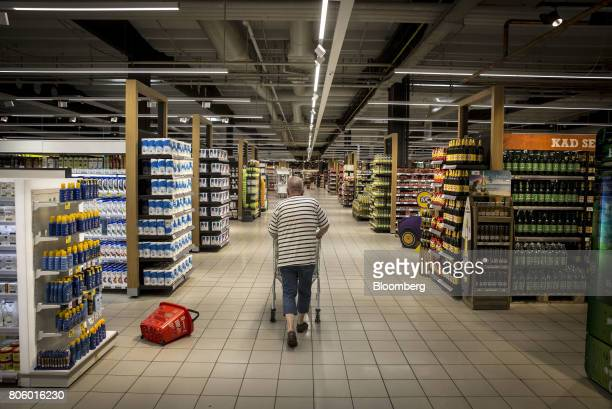 A customer wheels a shopping cart through the aisle inside a Super Konzum supermarket operated by Agrokor dd in Zagreb Croatia on Tuesday June 13...