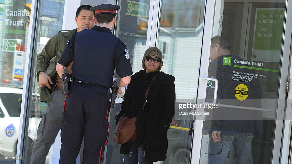 A customer who was in the bank centre is let outBank robbery at the TD Canada Trust on St Clair ave West today April 21st 2013...Two people were shot in the robbery and the robbers escaped with an unspecified amount of money in a stolen Honda...Police and forensics around the bank and witnesses being let out of the bank and ushered into taxis by bank empLoyees.