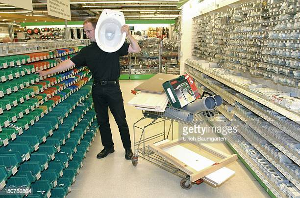 Customer with a trolley and a toilet bowl on his sholder at the shopping in a DIY store